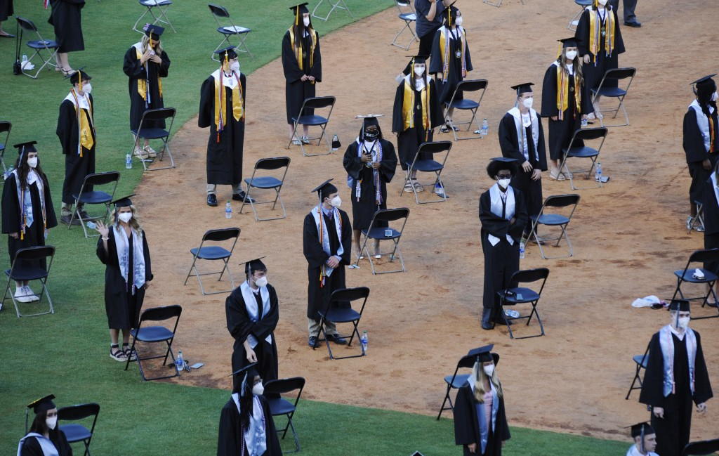 Seniors from Spain Park High School stand on a baseball field at a socially distanced graduation ceremony in Hoover, Ala., Wednesday, May 20, 2020. He...
