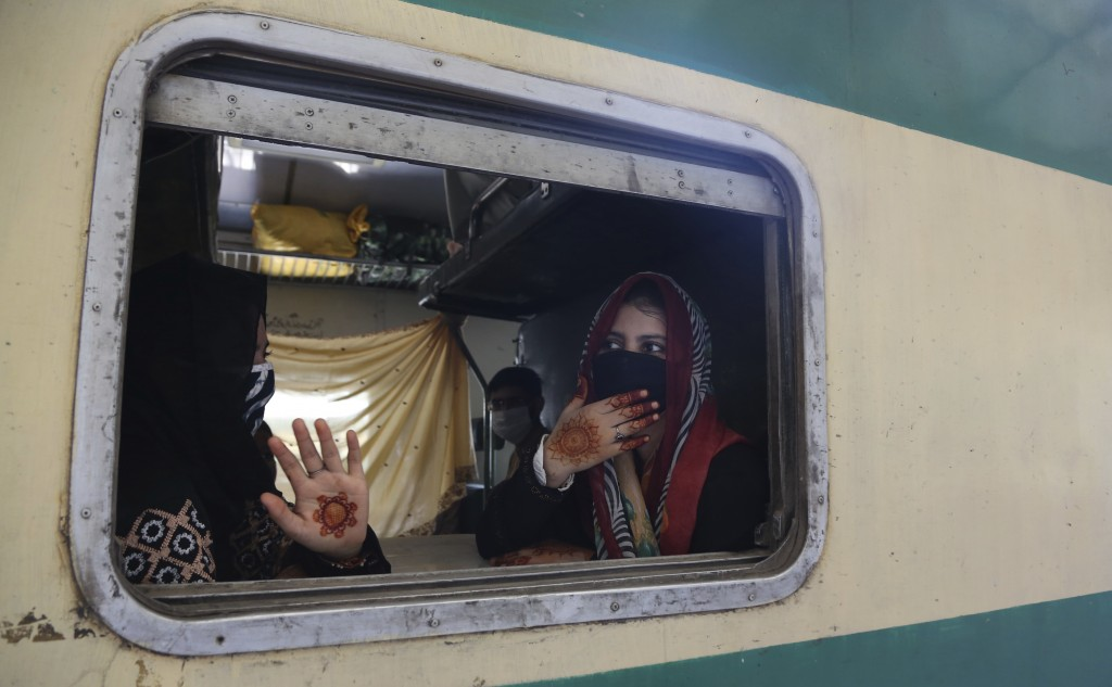 People wearing face masks travel on a train in Karachi, Pakistan, Wednesday, May 20, 2020. Authorities resumed railway service after a two month suspe...