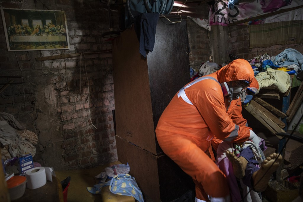 Piedrangel funeral home workers Jhoan Faneite and Luis Brito, both of Venezuela, remove the body of an 85-year-old retired carpenter who is suspected ...