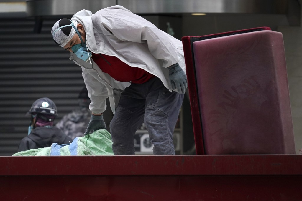 A man wearing a face mask to help curb the spread of the coronavirus works Wednesday, May 20, 2020, in Tokyo. Tokyo is still under a coronavirus state...