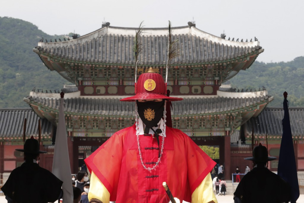 A South Korean Imperial guard waring a face mask stands during a reenactment of the Royal Guards Changing Ceremony, which had been suspended due to th...