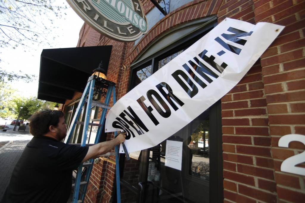 FILE - In this April 27, 2020, file photo, Jason Godbey hangs a banner over the entrance of Madison Chop House Grille as they prepare to shift from ta...