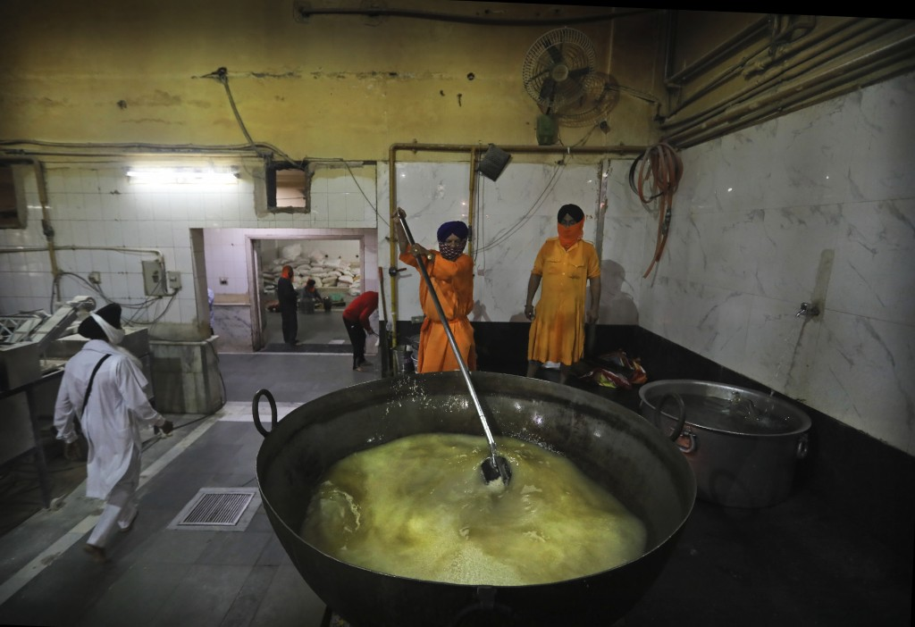 A Sikh cook stirs rice in a giant vessel in the kitchen hall of the Bangla Sahib Gurdwara in New Delhi, India, Sunday, May 10, 2020. The Bangla Sahib ...