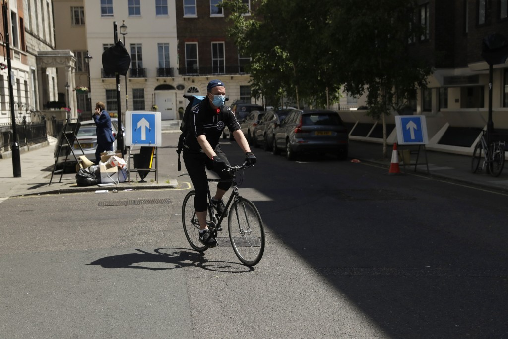 In this May 18, 2020, photo, medical courier Ben Gee, who works for The Doctors Laboratory, arrives to pick up a coronavirus test sample in London. Ge...