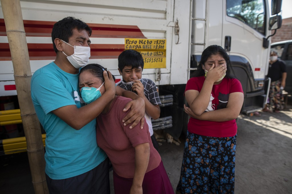 Family members grieve as they watch Piedrangel funeral home workers remove the body of a relative suspected of dying from the new coronavirus, in Lima...