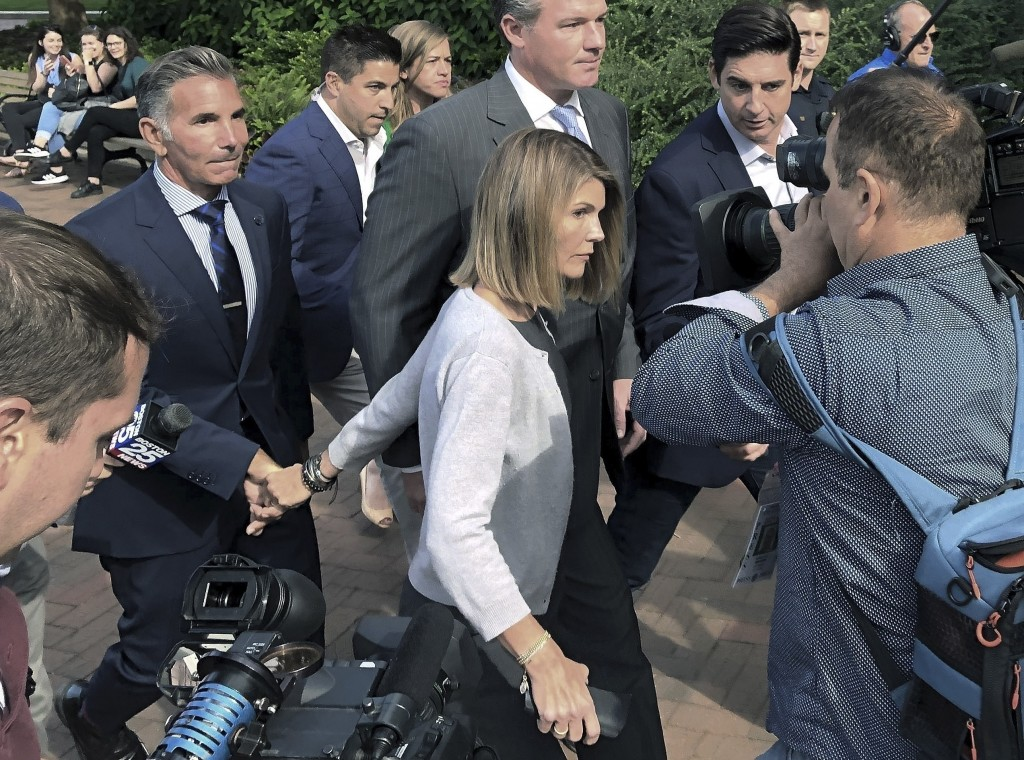 FILE - In this Aug. 27, 2019, file photo, Lori Loughlin departs federal court with her husband, clothing designer Mossimo Giannulli, left, in Boston, ...