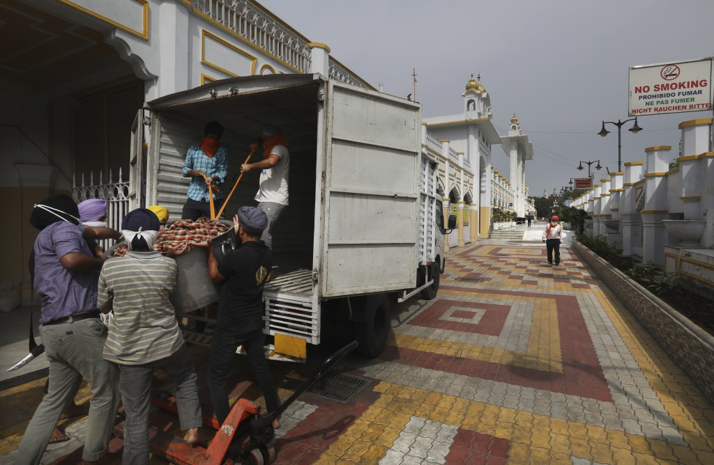 Sikh volunteers help to load food in a van from the kitchen hall of the Bangla Sahib Gurdwara for distribution, in New Delhi, India, Sunday, May 10, 2...