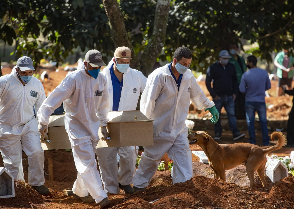 Cemetery workers in protective clothing carry the coffin of a COVID19 victim for burial at the Vila Formosa cemetery in Sao Paulo, Brazil, Wednesday, ...