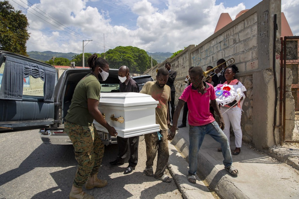 Cemetery workers carry the coffin with the body of 7-year-old Lovena Luberice to the Freres Public Cemetery in Port-au-Prince, Haiti, Wednesday, May 2...