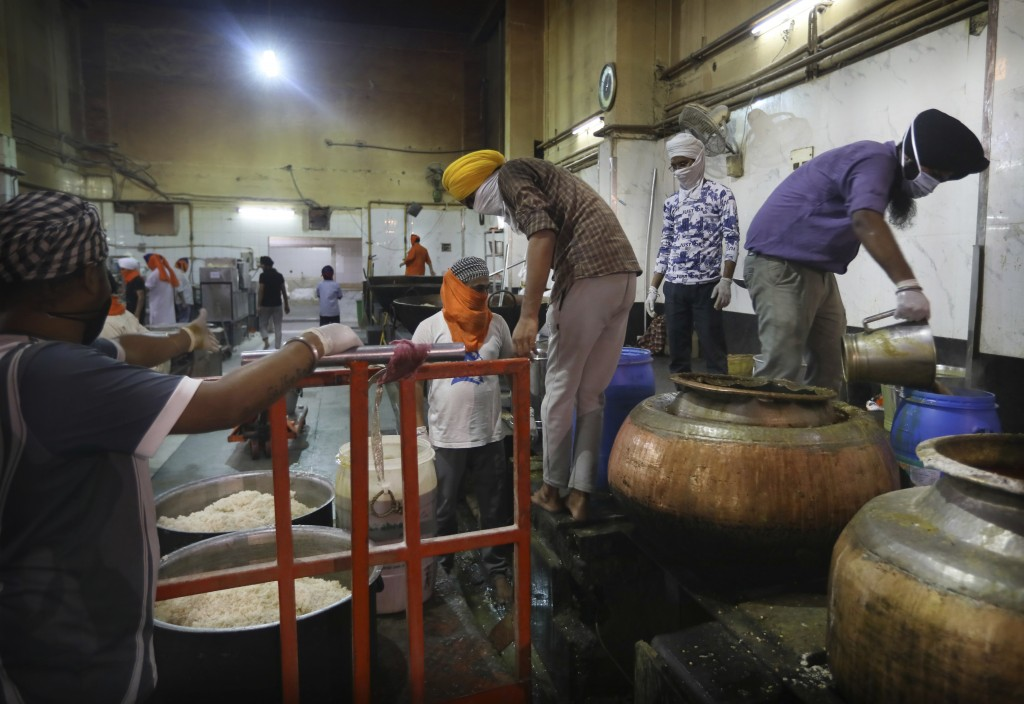 Sikh volunteers load prepared food onto a trolley to be taken out from the kitchen hall of the Bangla Sahib Gurdwara in New Delhi, India, Sunday, May ...