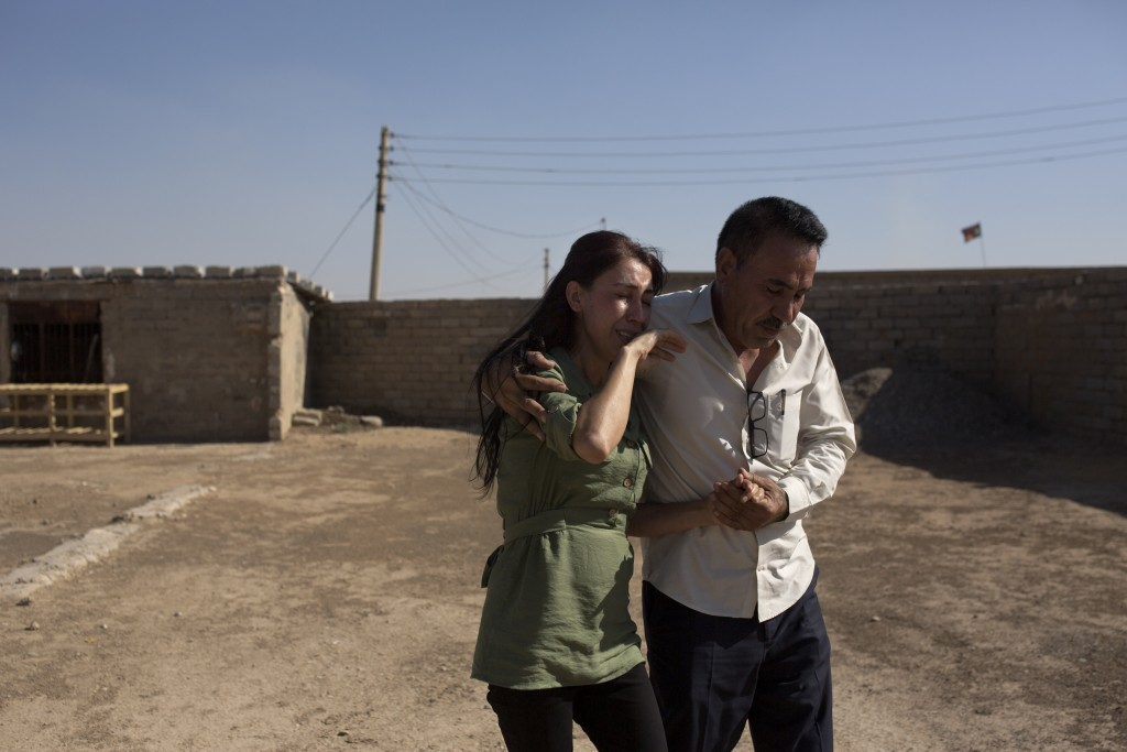 In this Aug. 31, 2019 photo, Layla Taloo is overcome with grief as her brother, Khalid, leads her away from the compound where she last saw her husban...