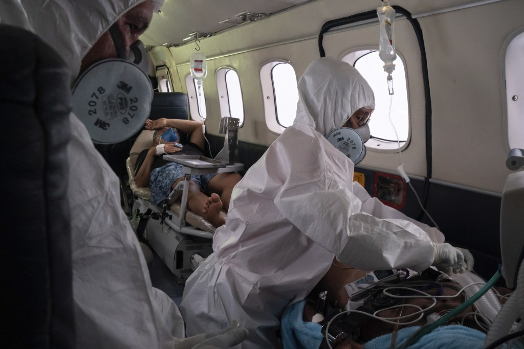 Doctor Daniel Siqueira, left, and nurse Janete Vieira monitor COVID-19 patients Abraão Lasmar, left, and Sildomar Castelo Branco onboard an aircraft a...