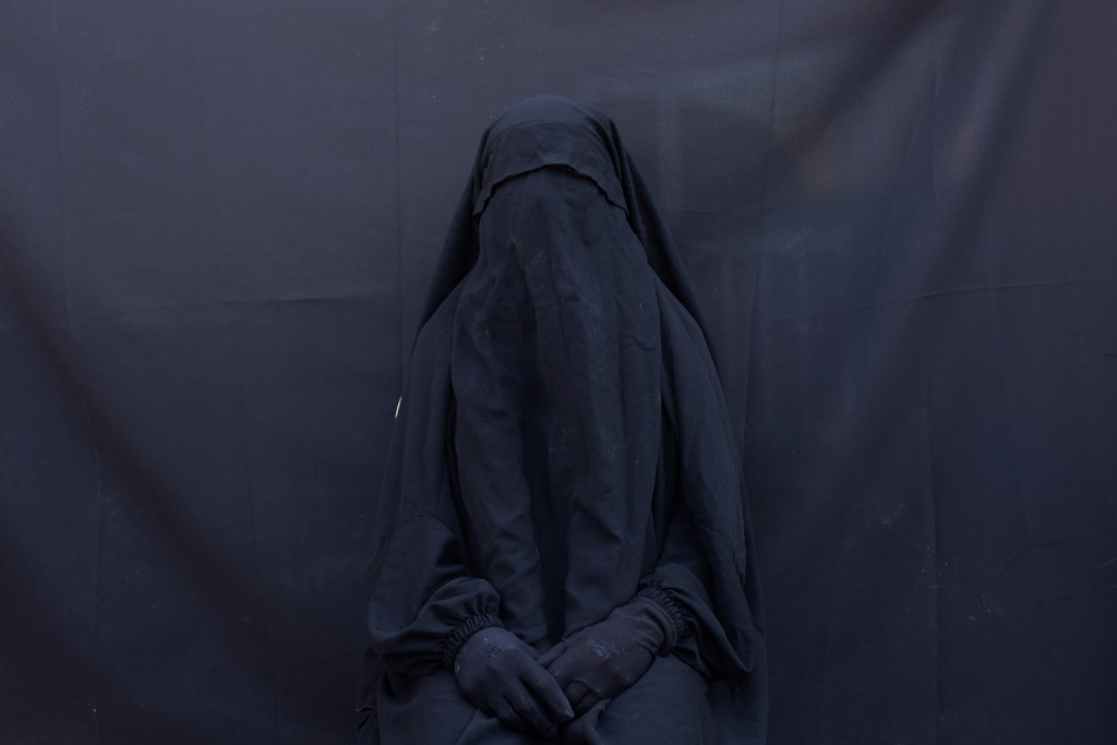 In this Sept. 9, 2019 photo, Yazidi Layla Taloo poses for a portrait in the full-face veil and abaya she wore while enslaved by Islamic State militant...