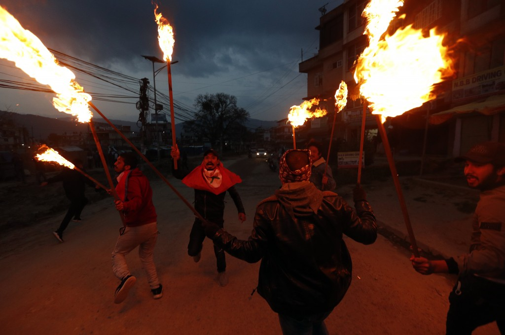 FILE - In this  Monday, May 11, 2020, file photo, students affiliated with Nepal Student Union walk with torches during a protest against the Indian g...