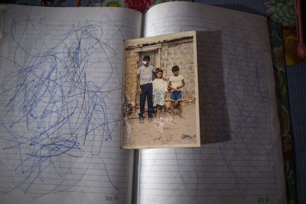 An old family snapshot of Jorge and Julia Lopez posing with their father Faustino Lopez, sits on a notebook of scribbled pages, in Lima, Peru, Tuesday...