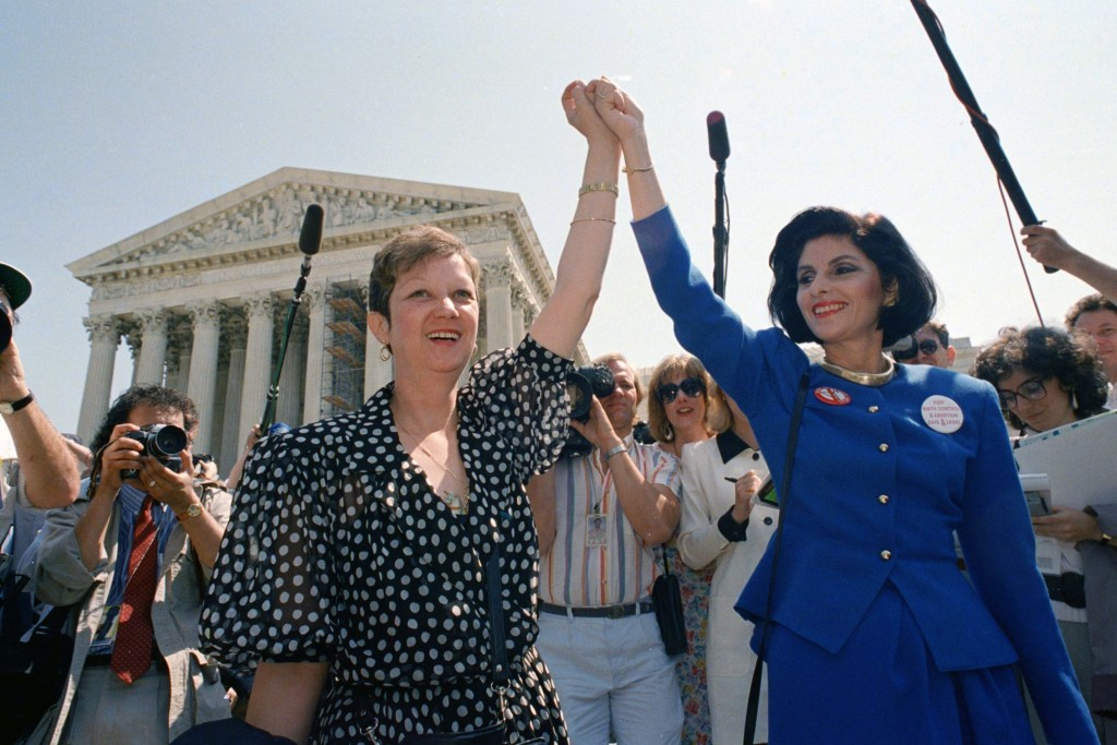 FILE - In this April 26, 1989 file photo, Norma McCorvey, Jane Roe in the 1973 court case, left, and her attorney Gloria Allred hold hands as they lea...