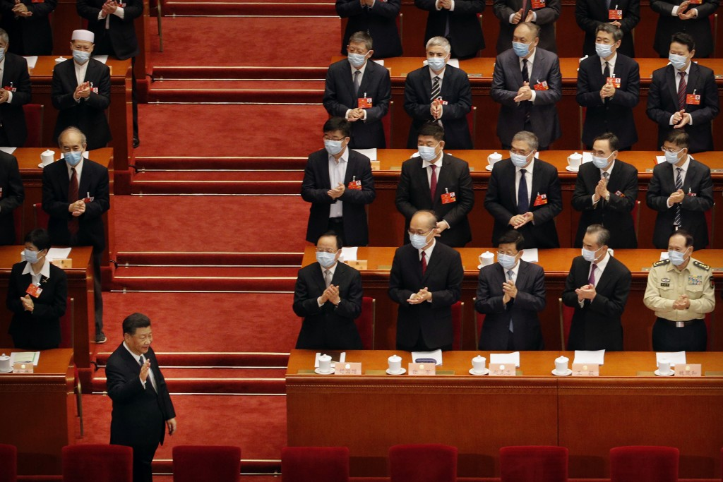 Chinese President Xi Jinping, left, gestures as he arrives for the opening session of the Chinese People's Political Consultative Conference (CPPCC) a...