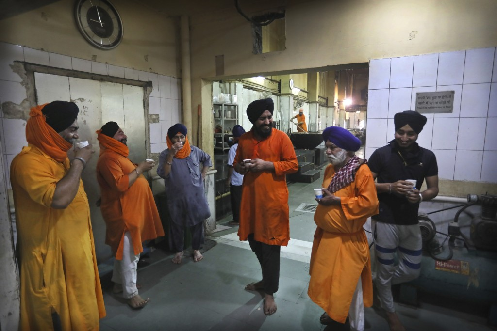 Sikh volunteers take a tea break in the kitchen hall of the Bangla Sahib Gurdwara in New Delhi, India, Sunday, May 10, 2020. The Bangla Sahib Gurdwara...