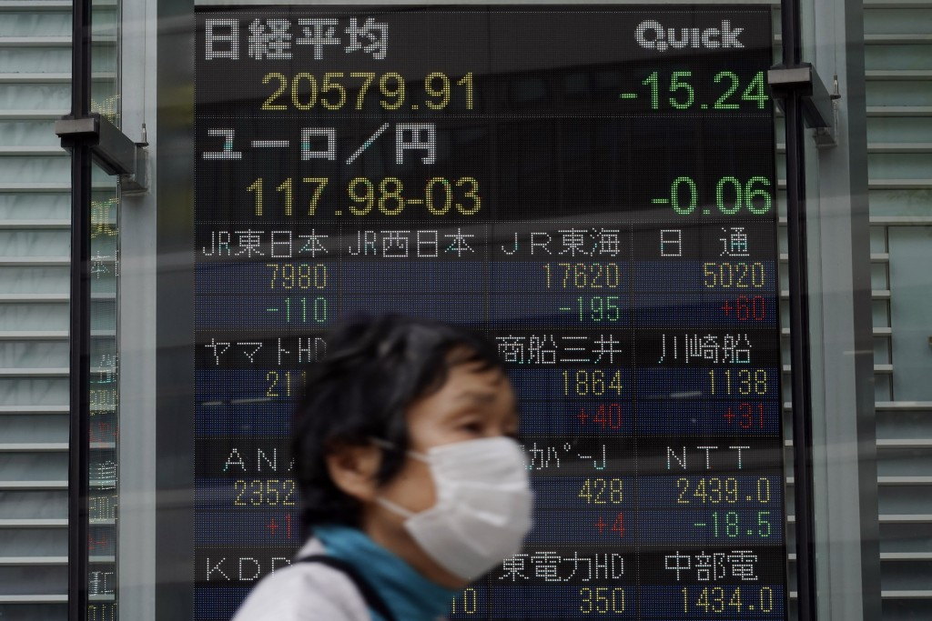 A masked woman walks past an electronic stock board showing Japan's Nikkei 225 index at a securities firm in Tokyo Thursday, May 21, 2020. Asian stock...
