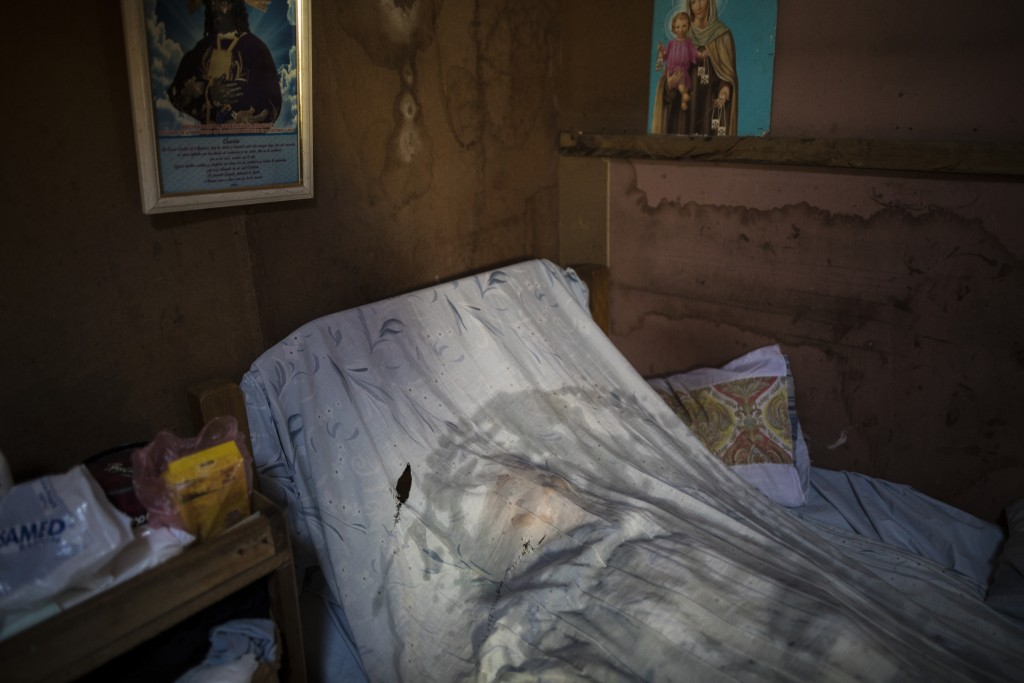 A bed sheet moistened with sodium hypochlorite covers the body of a person suspected to have died from the new coronavirus, in Lima, Peru, Wednesday, ...