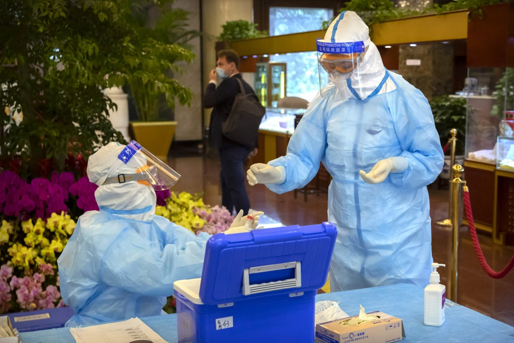 Workers in protective suits handle a COVID-19 test sample while testing foreign journalists covering a press conference for China's National People's ...