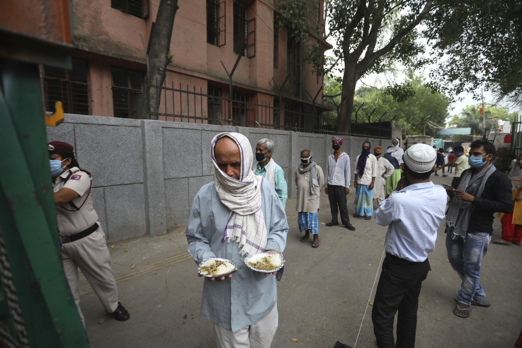An impoverished man walks after receiving food prepared by the Bangla Sahib Gurdwara kitchen as others wait in a queue in New Delhi, India, Sunday, Ma...