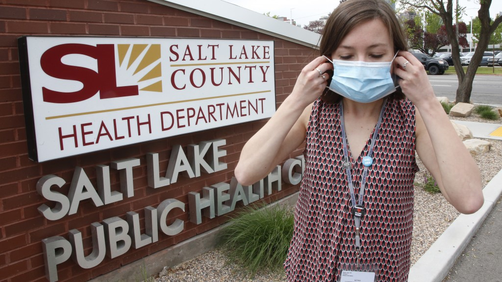 In this Tuesday, May 19, 2020, photo, health investigator Mackenzie Bray adjusts her mask at the Salt Lake County Health Department, in Salt Lake City...