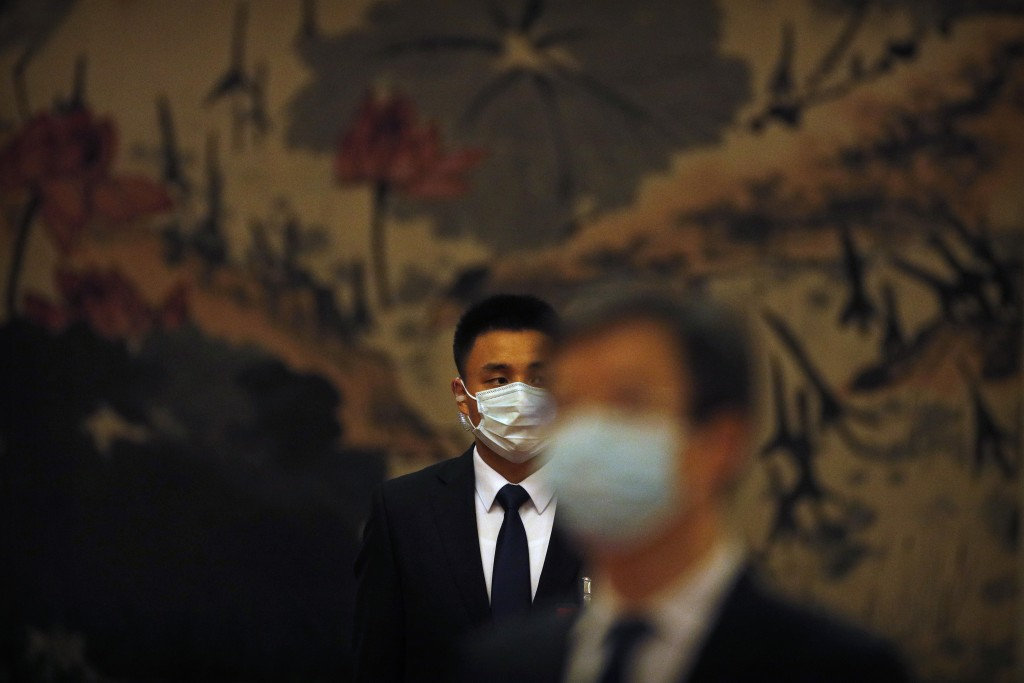 A security officer wearing a face mask to protect against the new coronavirus stands guard before the opening session of the Chinese People's Politica...