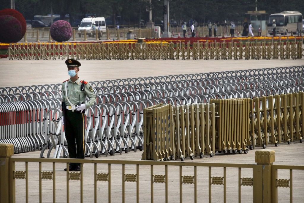 A Chinese paramilitary policeman wearing a face mask to protect against the new coronavirus stands guard on Tiananmen Square before the opening sessio...