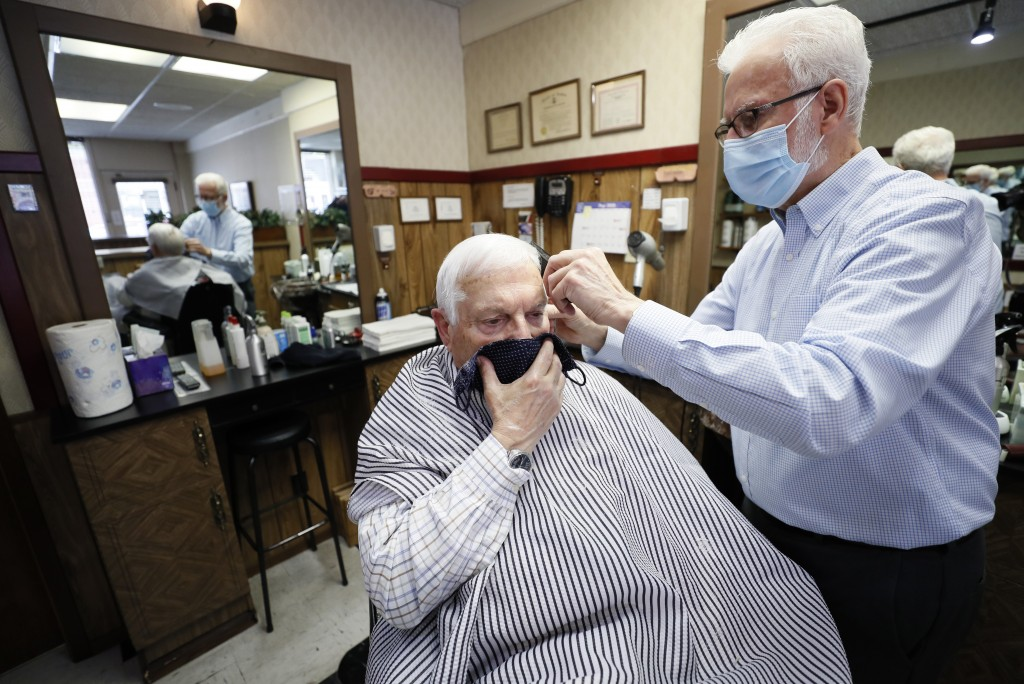 FILE - In this May 15, 2020 file photo, barber Lannie Hale cuts Bob Mitchell's hair at his Waveland Barber Stylist shop in Des Moines, Iowa.  With mor...