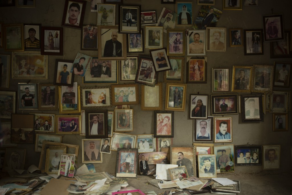In this Sept. 12, 2019 photo, pictures of Yazidis slain in 2014 by Islamic State militants are found in a small room at the Lalish shrine in northern ...