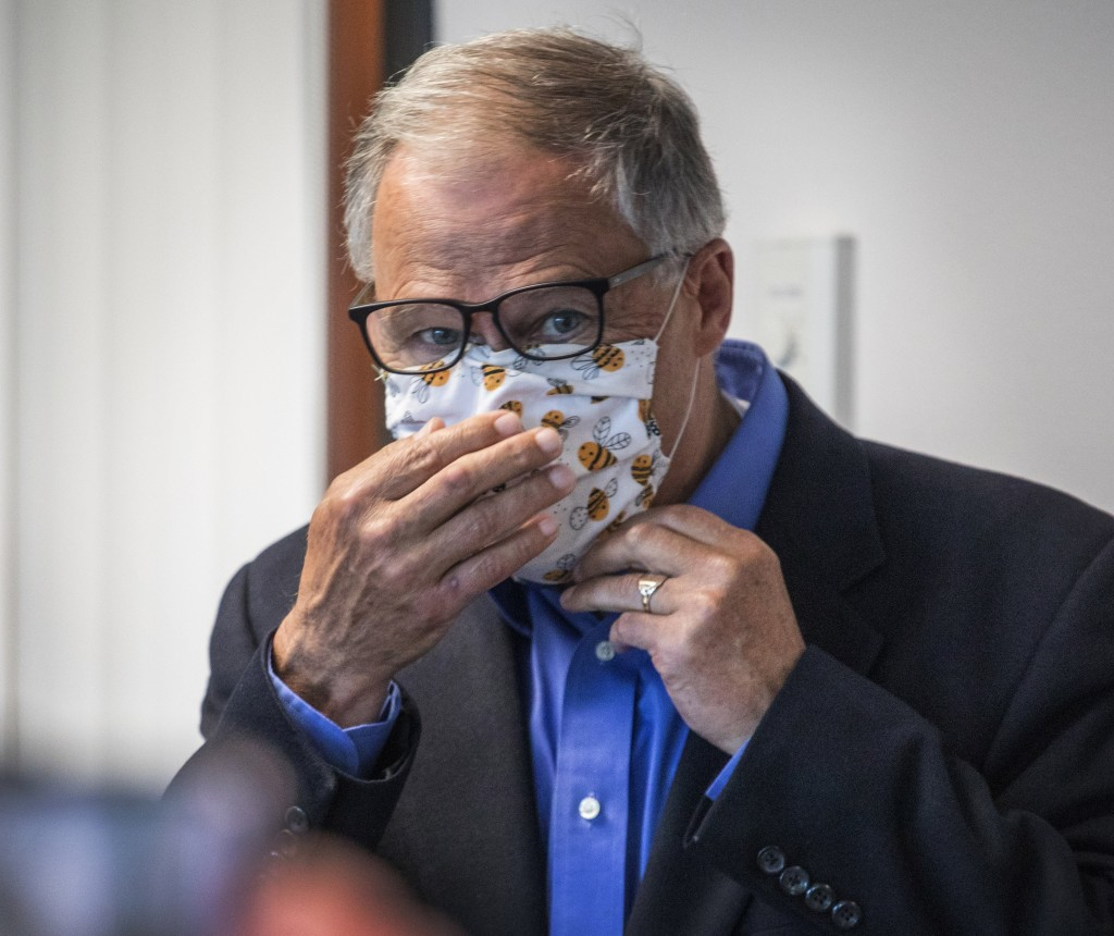Washington Gov. Jay Inslee puts on his face mask after speaking to the media, Wednesday, May 20, 2020, in Tumwater, Wash., about the state's effort at...