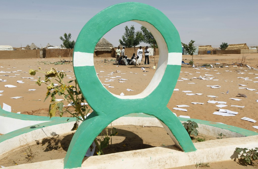 FILE - In this Sunday, March 21 2009 file photo, Sudanese refugees gather behind the Oxfam logo at the site of the looted compound of the expelled Bri...