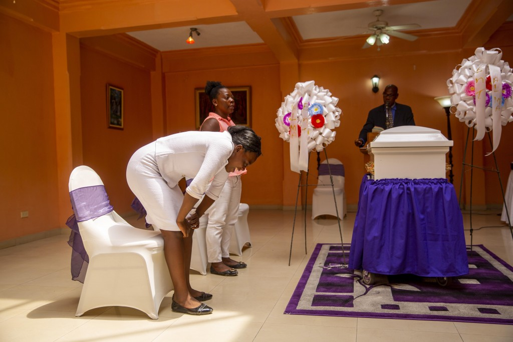 Ermilia Luberice, left, mourns next to her friend Yolande Jean Louis, during the funeral of her 7-year-old daughter Lovena Luberice at the Alcero Marc...