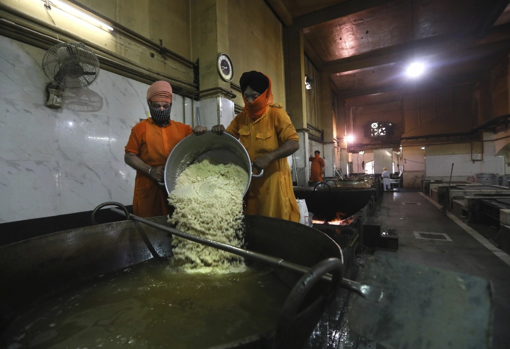 A Sikh volunteer pours rice into a giant vessel in the kitchen hall of the Bangla Sahib Gurdwara in New Delhi, India, Sunday, May 10, 2020. The Bangla...