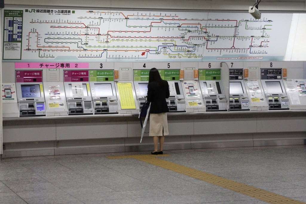 A woman buys a train ticket at quiet Yokohama station in Yokohama, Kanagawa prefecture, near Tokyo, Thursday, May 21, 2020. Kanagawa is still under a ...