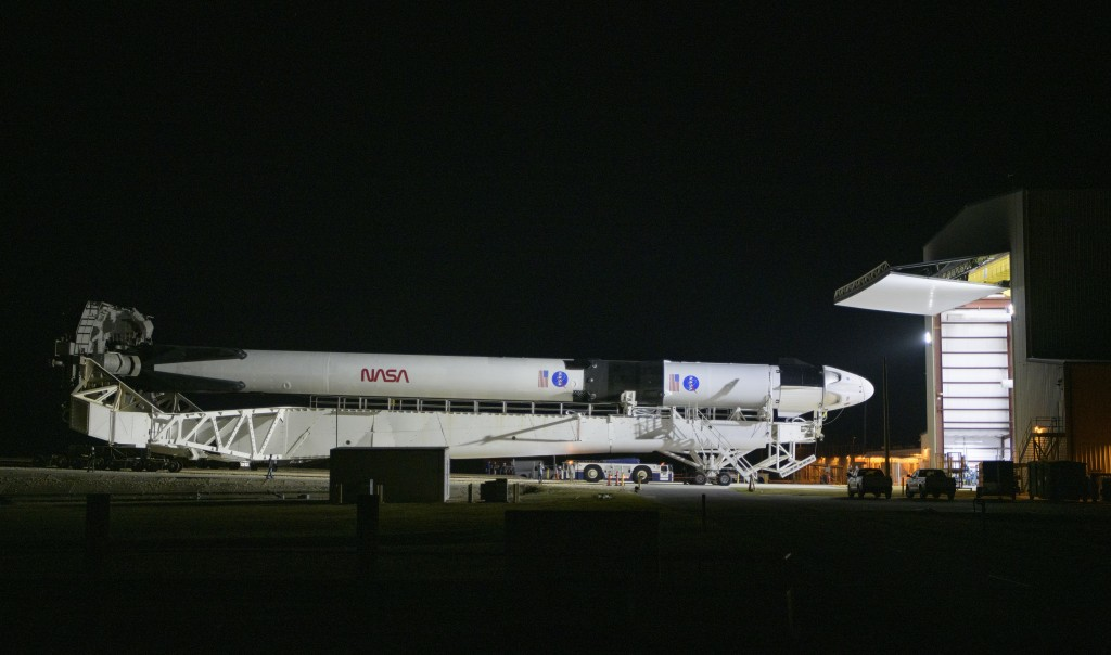 A SpaceX Falcon 9 rocket with the company's Crew Dragon spacecraft is rolled out of the horizontal integration facility at Launch Complex 39A as prepa...