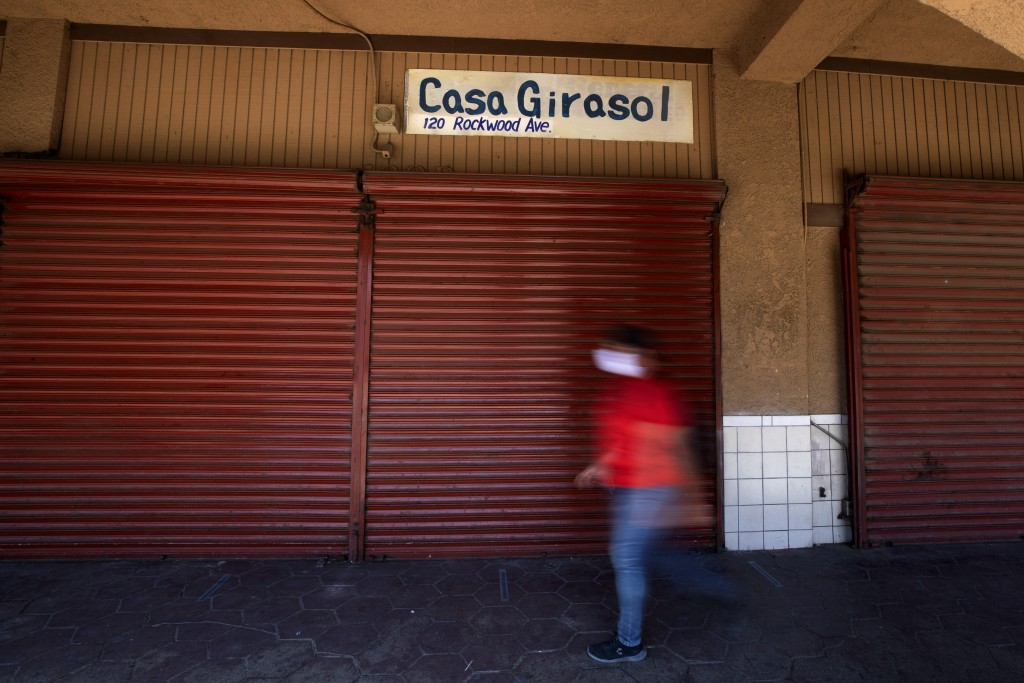 A man wears a mask as he passes closed storefronts, Wednesday, May 20, 2020, in Calexico, Calif. As much of California inches toward businesses reopen...