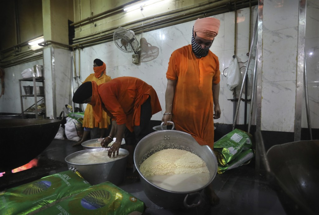 Sikh volunteers wash rice before it is coked in the kitchen hall of the Bangla Sahib Gurdwara in New Delhi, India, Sunday, May 10, 2020. The Bangla Sa...