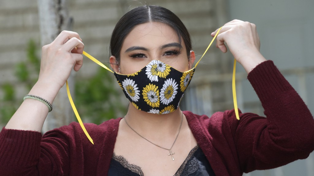 In this Monday, May 18, 2020, photo, Anissa Archuleta wears her mask at her home in Midvale, Utah. Jaime Ortega and her two daughters Anissa Archuleta...