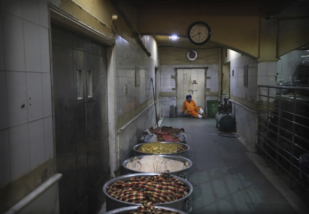 A Sikh cook rests as large vessels containing cooked rice lie covered with cloth in the kitchen hall of the Bangla Sahib Gurdwara in New Delhi, India,...