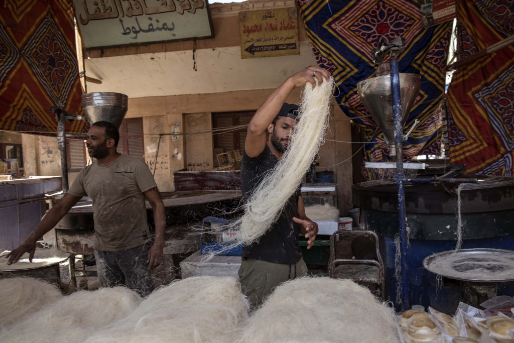 In this May 9, 2020 photo, 28-year-old football defender Mahrous Mahmoud, right, makes Ramadan sweets, in Manfalut, a town 350 kilometers (230 miles) ...