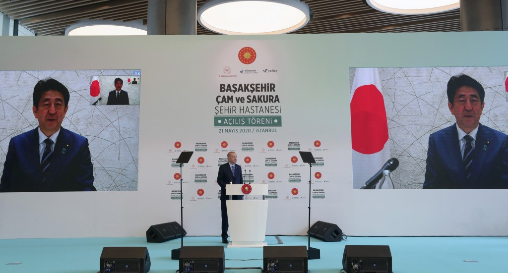 In this photo provided by the Turkish Presidency, Turkey's President Recep Tayyip Erdogan speaks to Japanese Prime Minister Shinzo Abe via video link,...