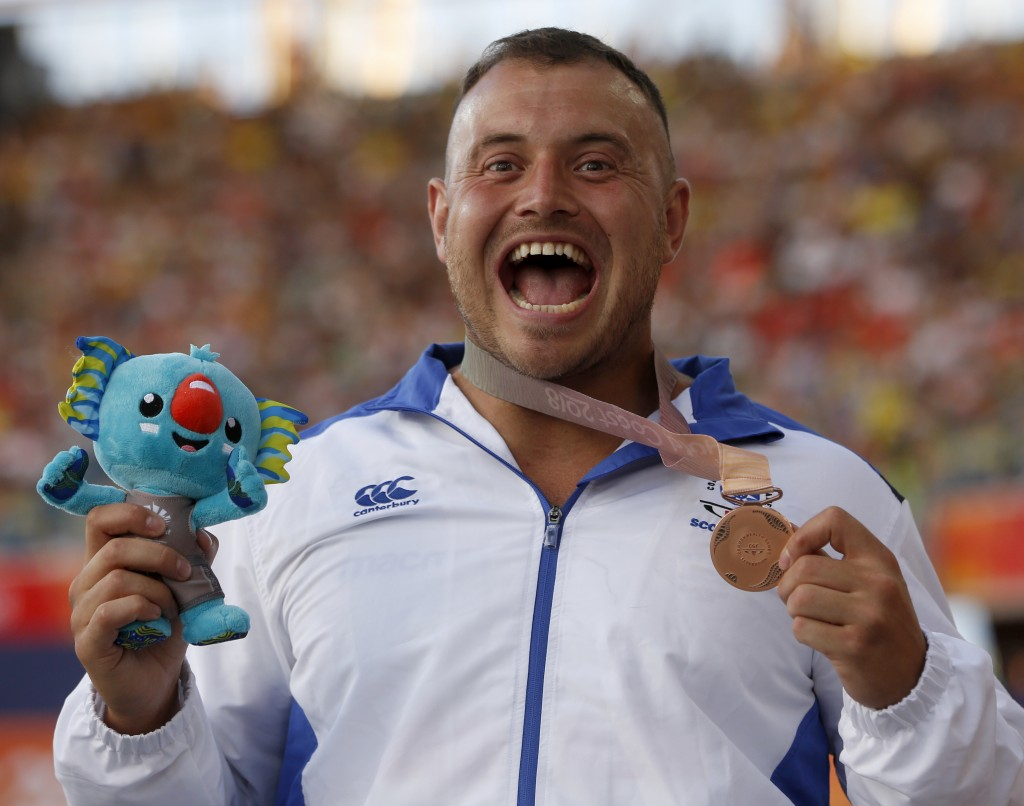 FILE - In this April 8, 2018 file photo men's hammer throw bronze medalist Mark Dry of Scotland reacts on the podium at the Carrara Stadium during the...
