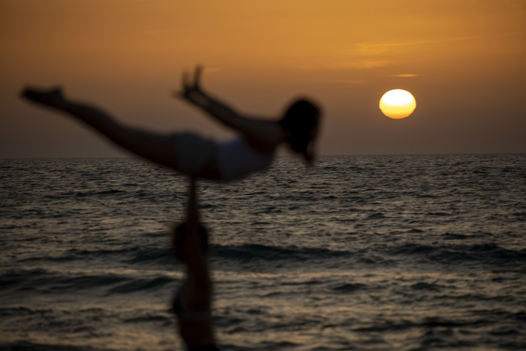 Two women practice acrobatics at sunset on the Mediterranean Sea, while many beachgoers blocked out fear of the coronavirus as temperatures hit 38 deg...