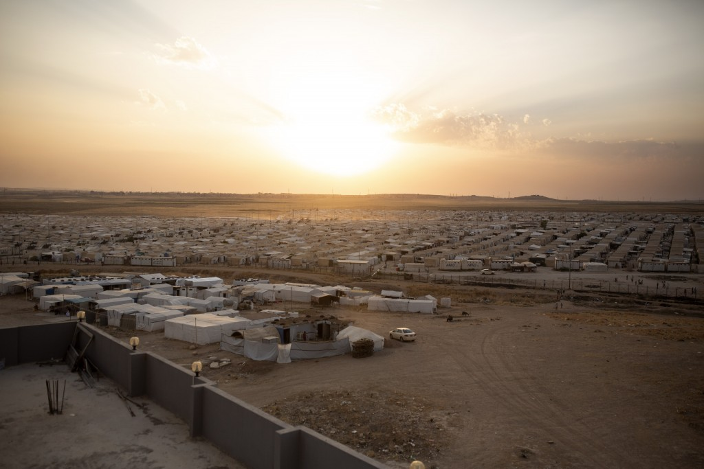 In this Aug. 24, 2019 photo, the sun sets over Sharia Camp, where Yazidis displaced by Islamic State militants are housed near Dohuk, Iraq. Some 3,500...