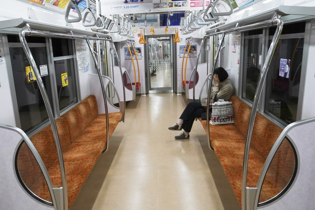 A woman rides an empty subway Thursday, May 21, 2020, in Tokyo. Tokyo is still under a coronavirus state of emergency until the end of May though ther...