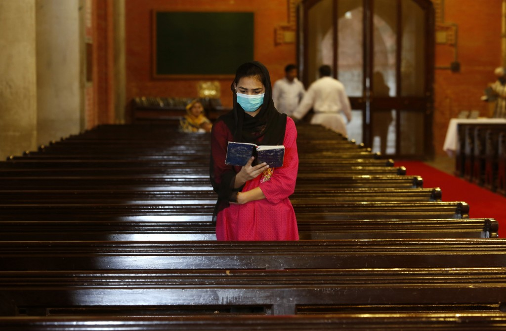 A Christian wears a protective mask as she attends Mass while maintaining a social distance at the Cathedral Church of the Resurrection in Lahore, Pak...