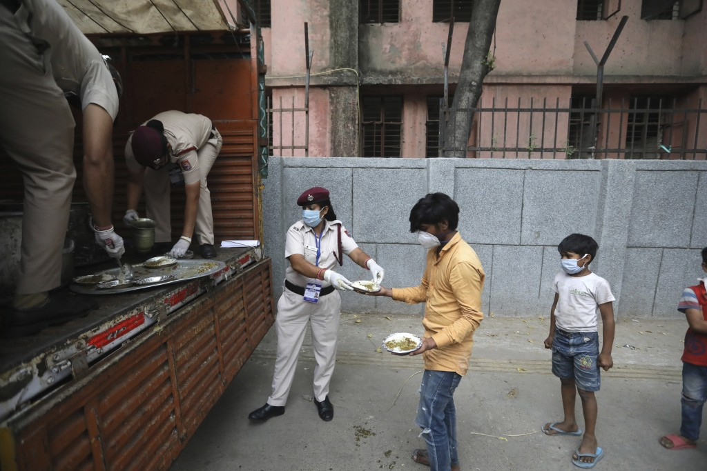 Delhi policewomen distribute food prepared by the Bangla Sahib Gurdwara kitchen in an impoverished locality in New Delhi, India, Sunday, May 10, 2020....