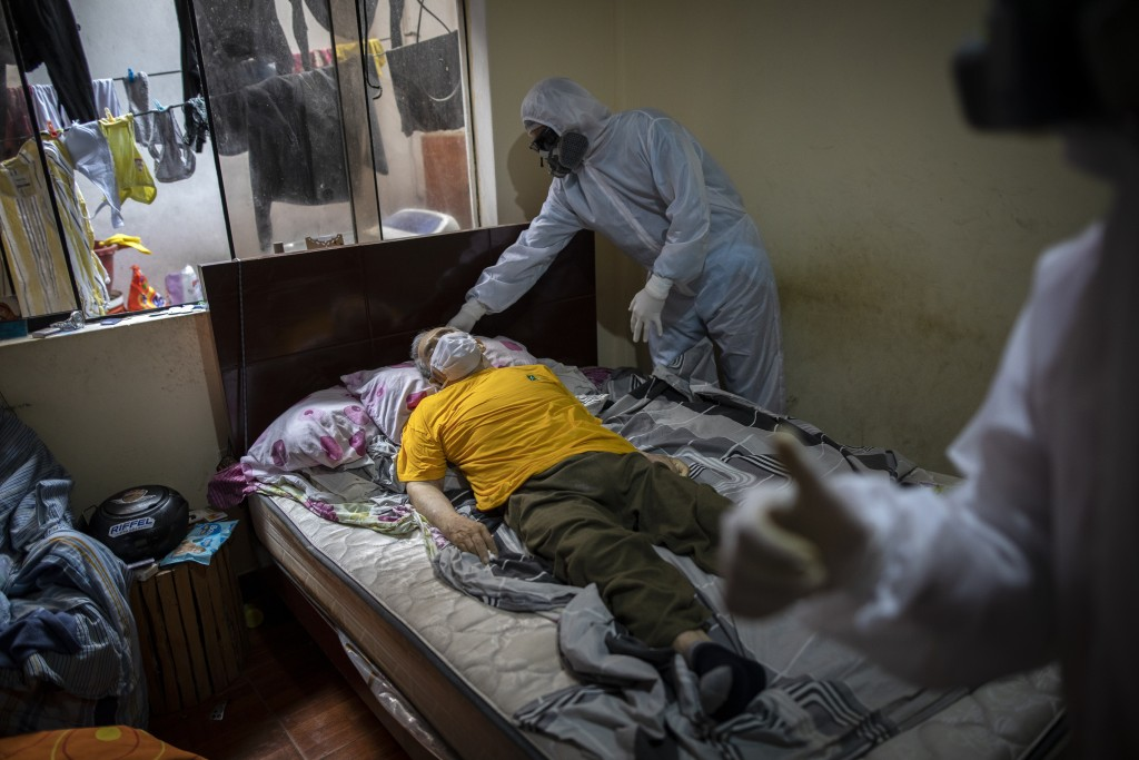 Piedrangel funeral home workers prepare to remove the body of a man suspected to have died from the new coronavirus, from his home in Lima, Peru, Frid...